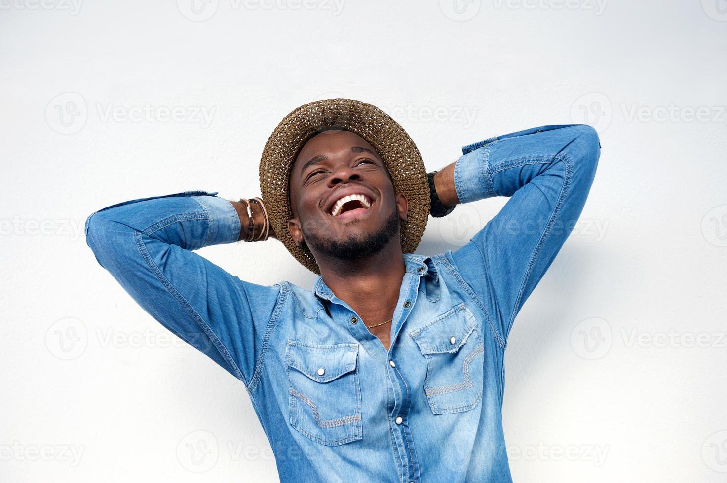 jonge man lachen met handen achter het hoofd foto