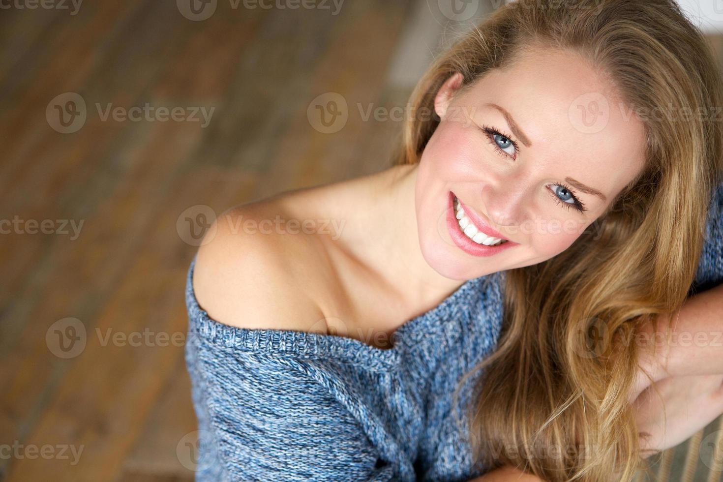 mooie jonge vrouw die thuis glimlacht foto