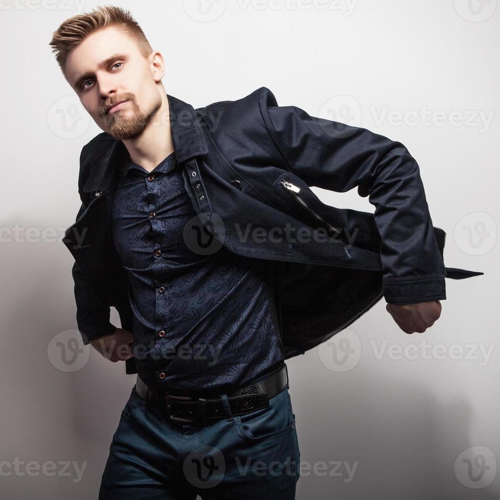 elegante jonge knappe man in zwarte jas. studio mode portret. foto