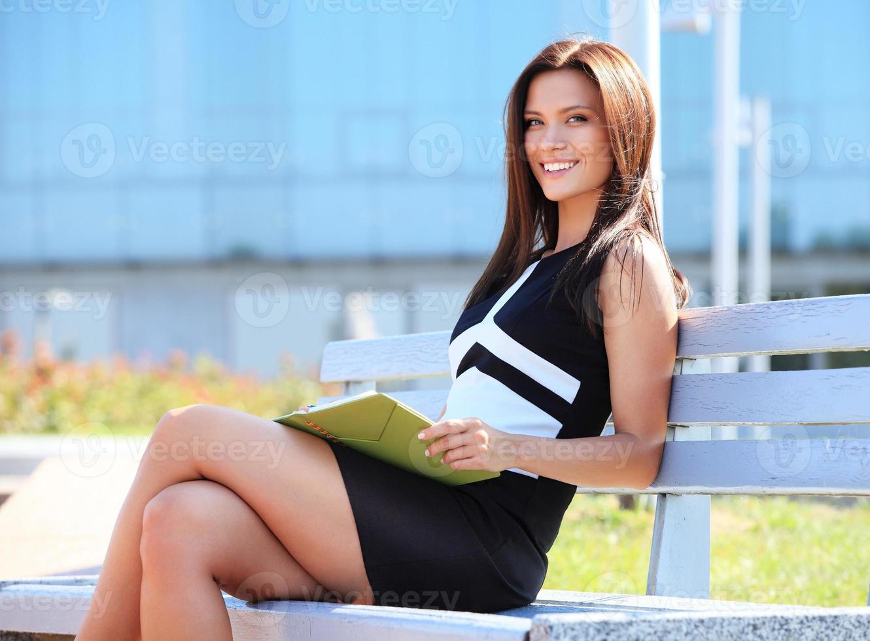 jonge professionele vrouw zittend op een houten bankje in het park foto