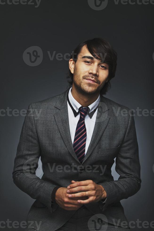 zelfverzekerde jonge zakenman tegen zwarte achtergrond foto