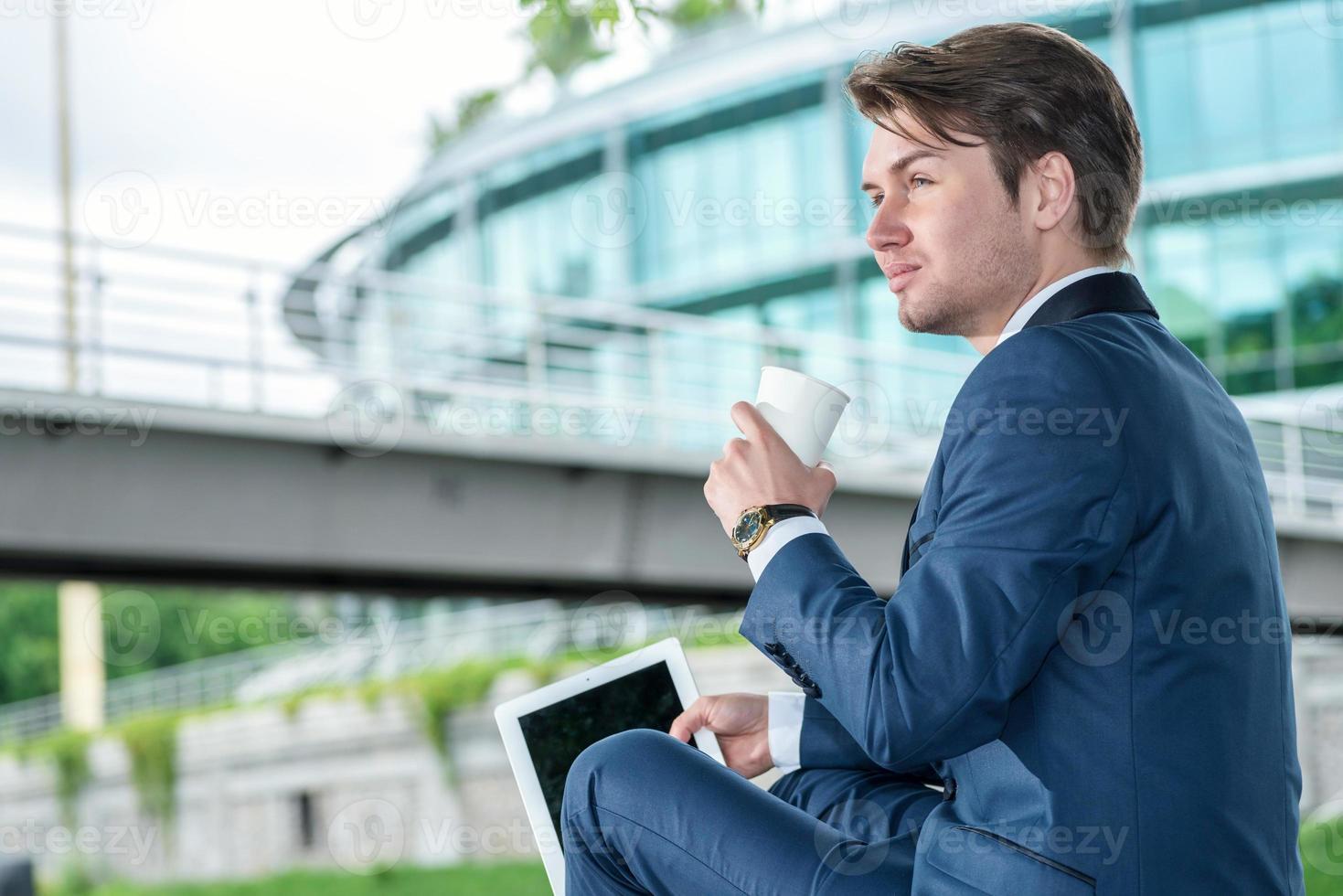 zakenman buiten zitten en koffie drinken en werken de foto