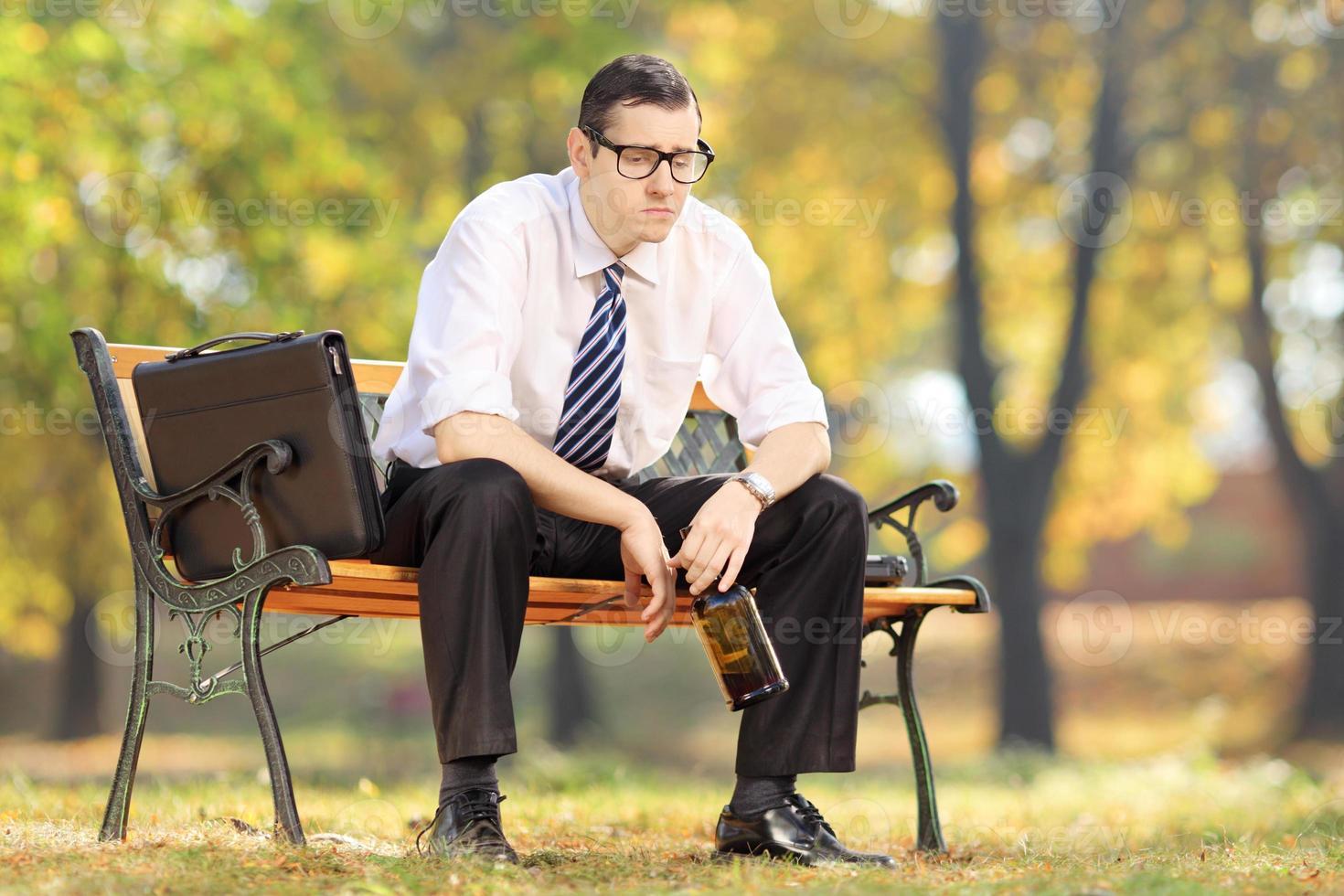 teleurgesteld zakenman zittend op een houten bankje, in park foto