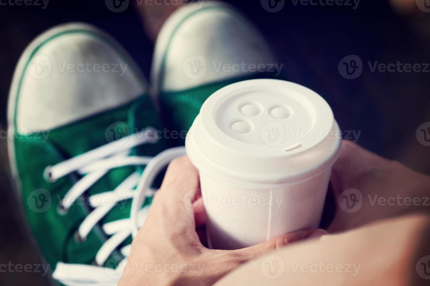 jonge vrouw koffie drinken uit wegwerp beker foto
