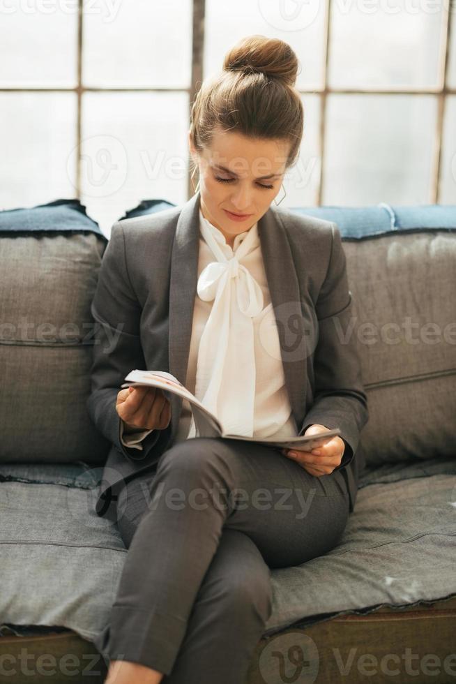 zakenvrouw lezing tijdschrift in loft appartement foto