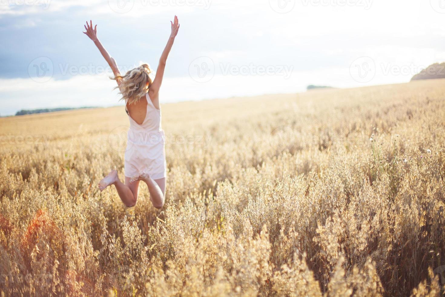 vrouw in een tarweveld met uitgestrekte armen foto