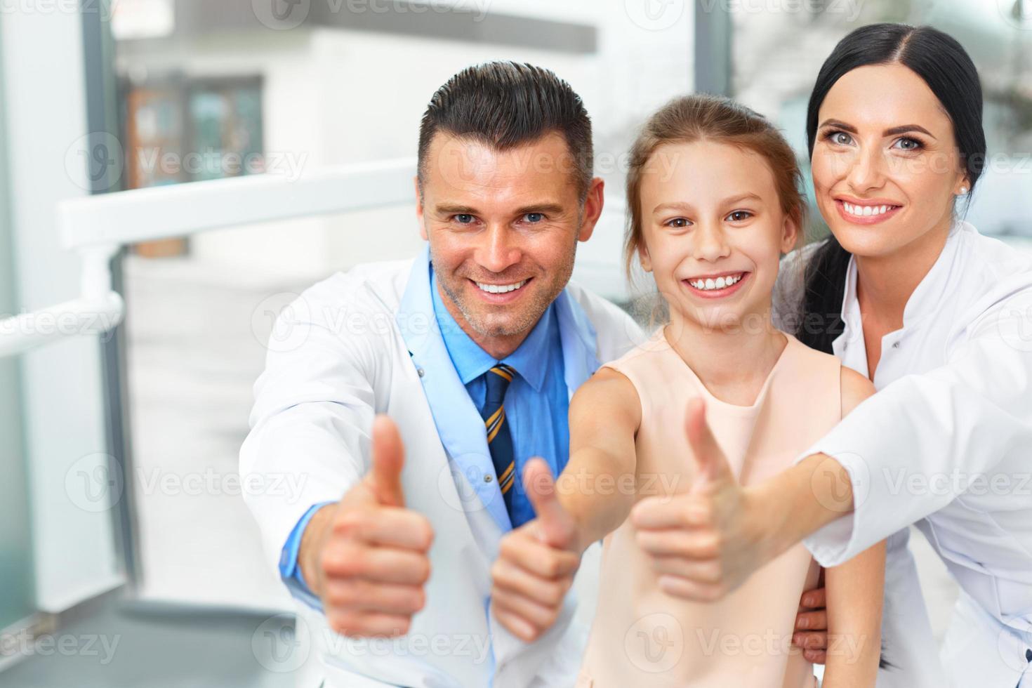 tandarts arts, assistent en klein meisje glimlachen allemaal op camera foto