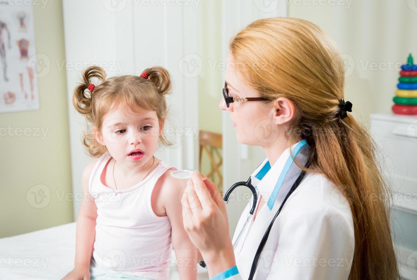 kinderarts die medicijn geeft aan meisje foto