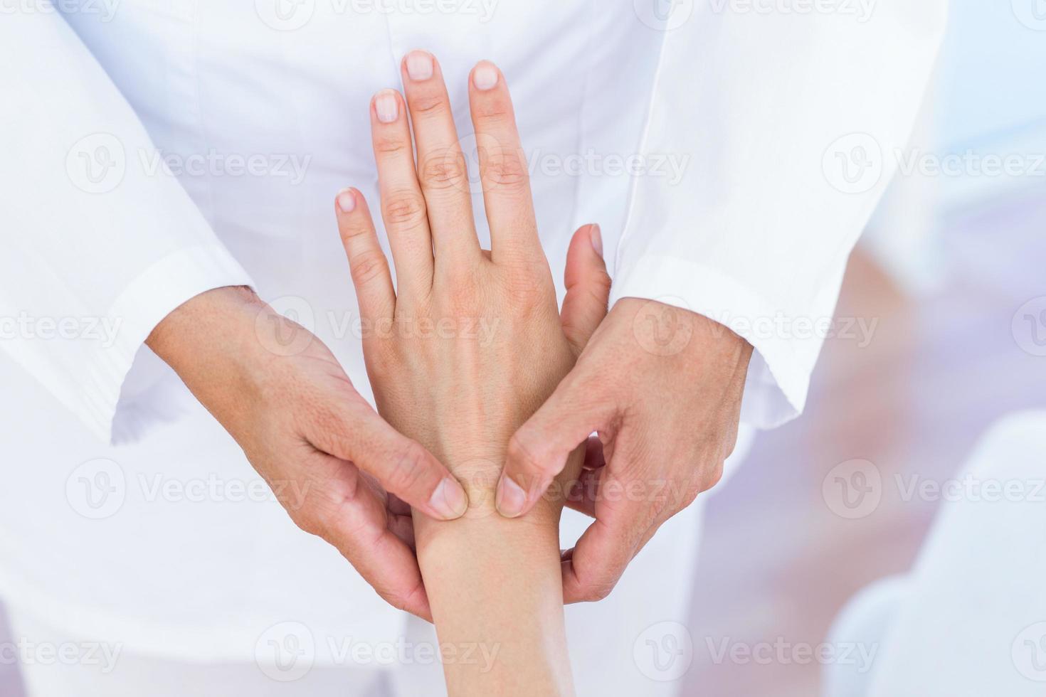 arts die de pols van haar patiënten onderzoekt foto
