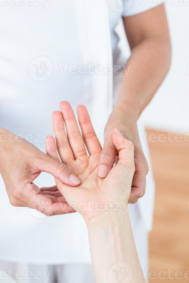 fysiotherapeut die de hand van haar patiënten onderzoekt foto