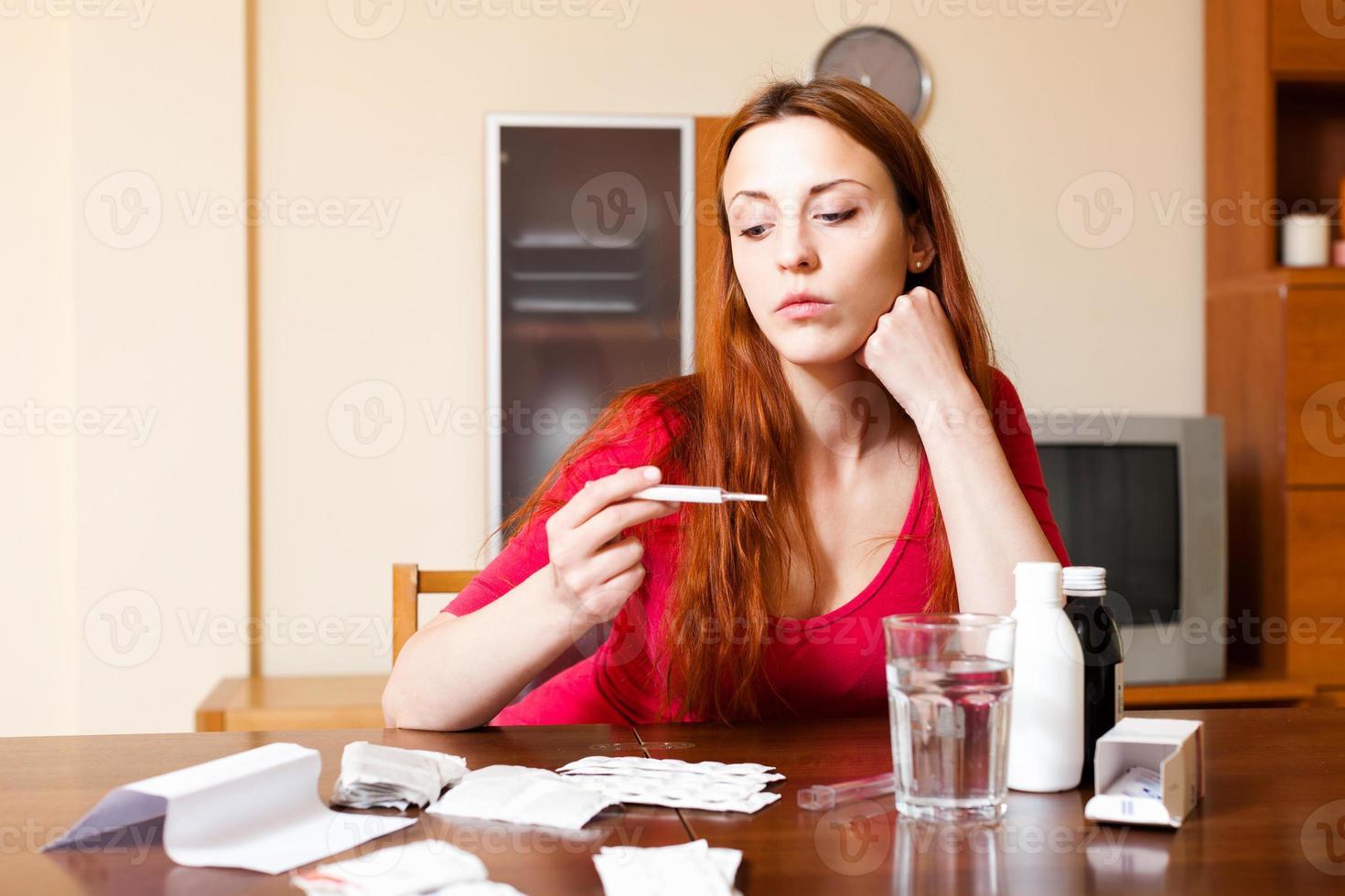 triest vrouw met thermometer in de woonkamer thuis foto