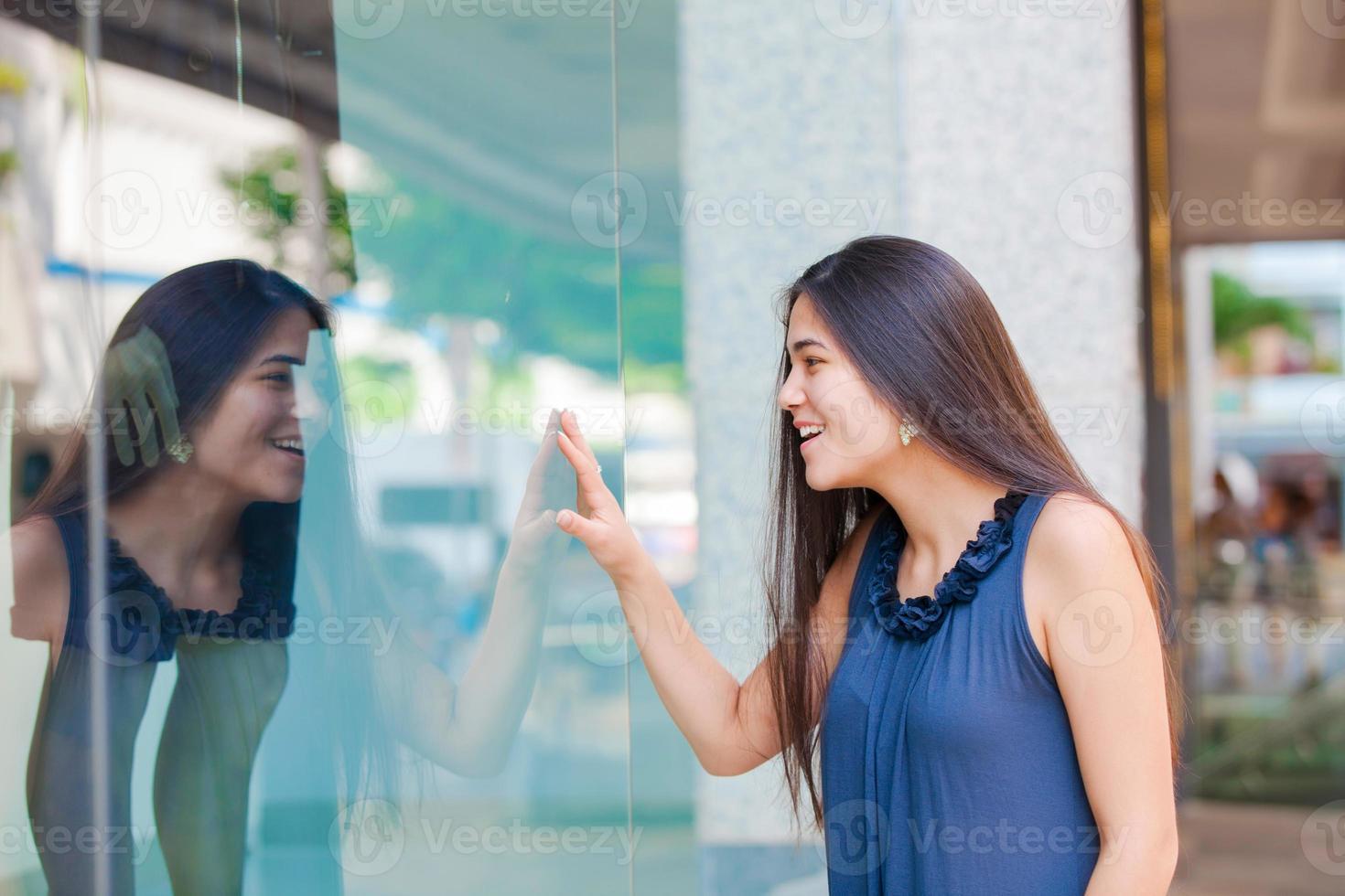 biracial tiener meisje raam winkelen in de stedelijke omgeving van de stad foto