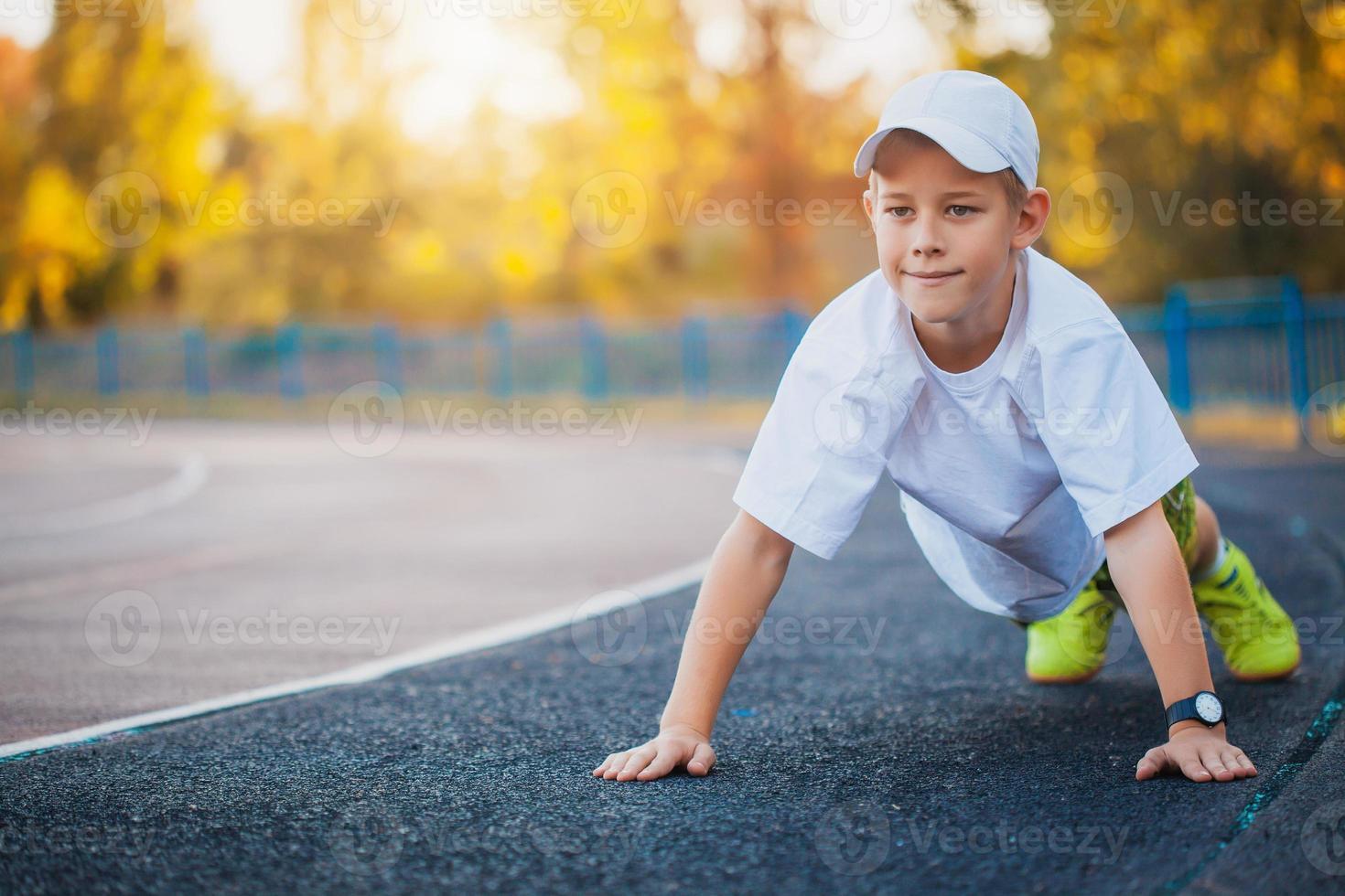 jongen tiener sport oefeningen doen op een stadion foto