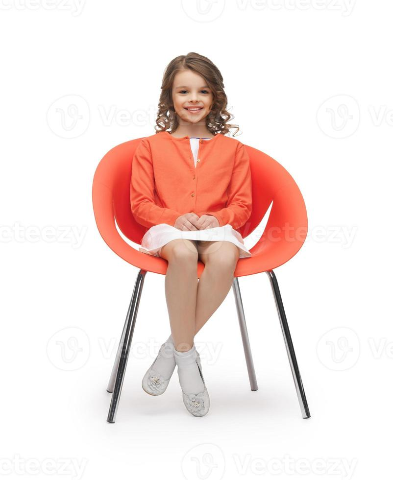 pre-tiener meisje in casual kleding zittend op een stoel foto