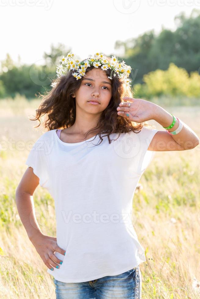 tienermeisje met een krans van madeliefjes in veld foto
