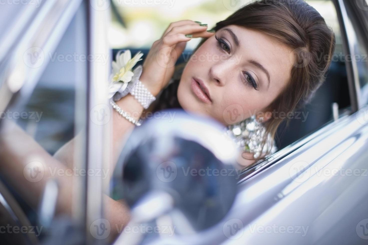tiener die make-up in auto controleert foto