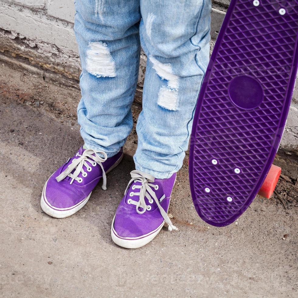 tiener in blauwe jeans staat met skateboard foto