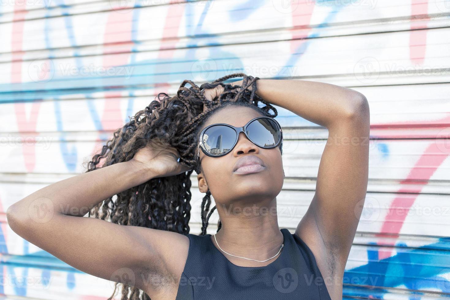 stedelijk portret van mooie Afrikaanse vrouw met zonnebril, kapsel. foto