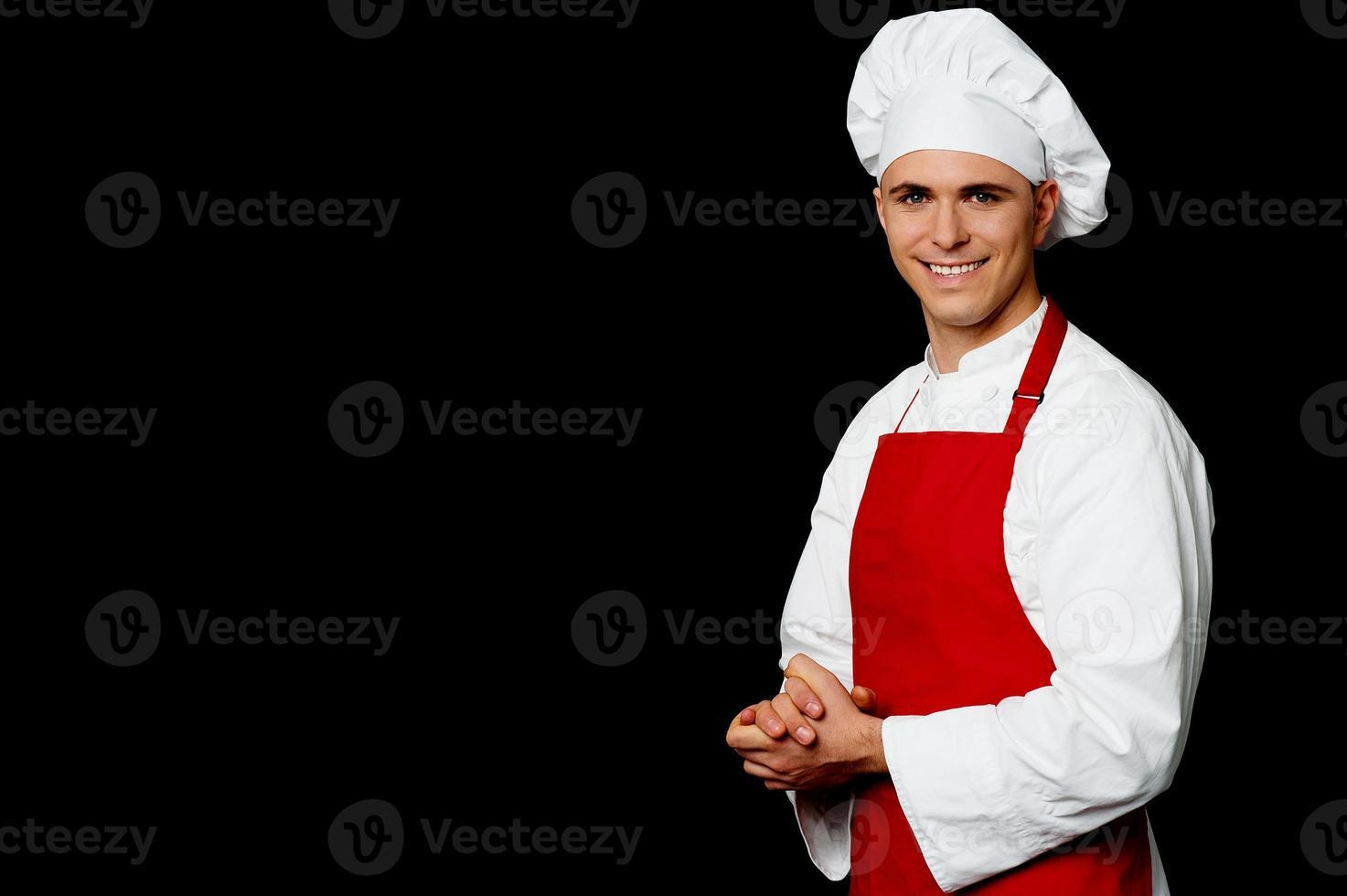geïsoleerde mannelijke chef-kok op zwarte achtergrond foto