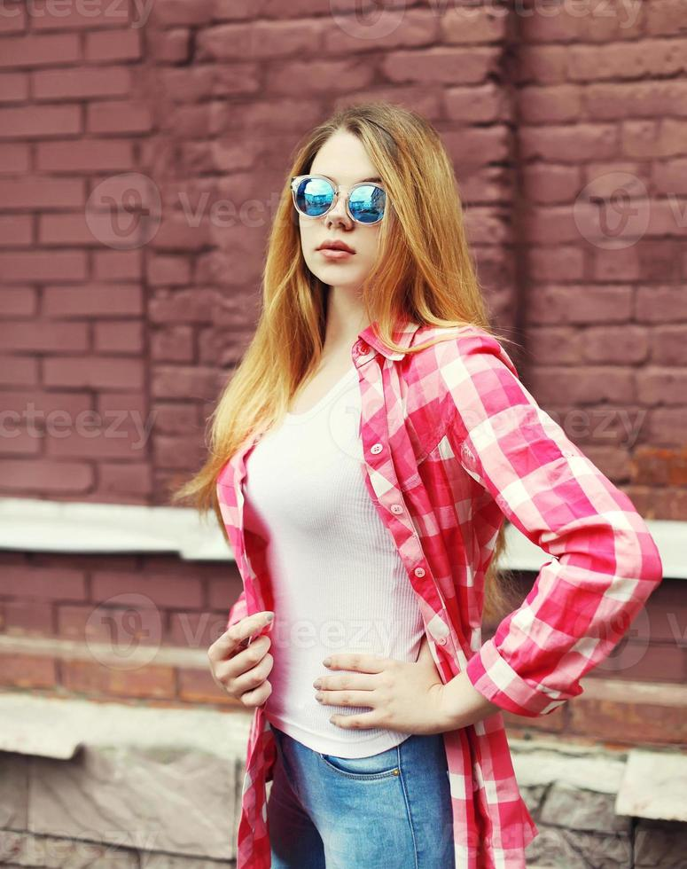 portret jong meisje dat een geruit overhemd en zonnebril draagt ove foto