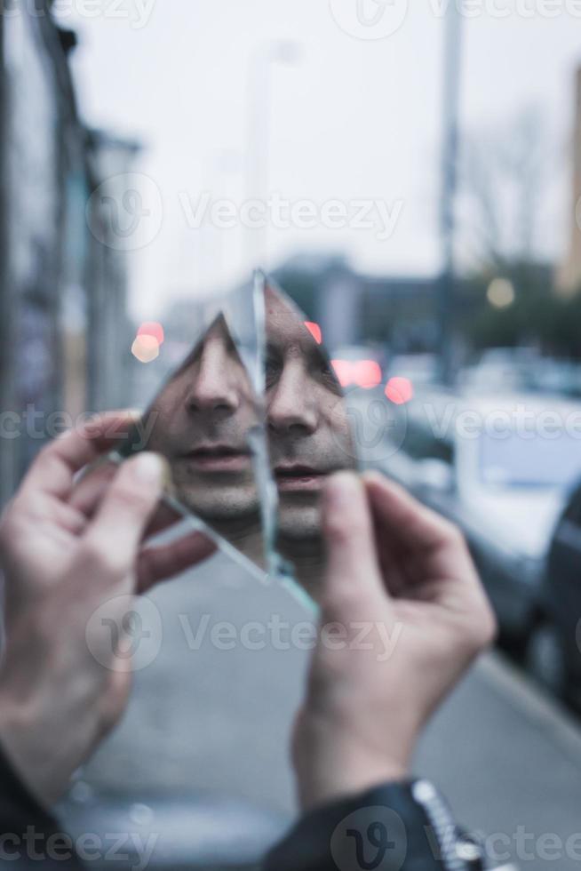 punk man kijkt naar zichzelf in een verbrijzelde spiegel foto