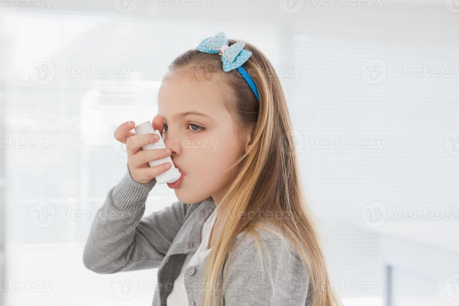 klein meisje met behulp van haar inhalator foto