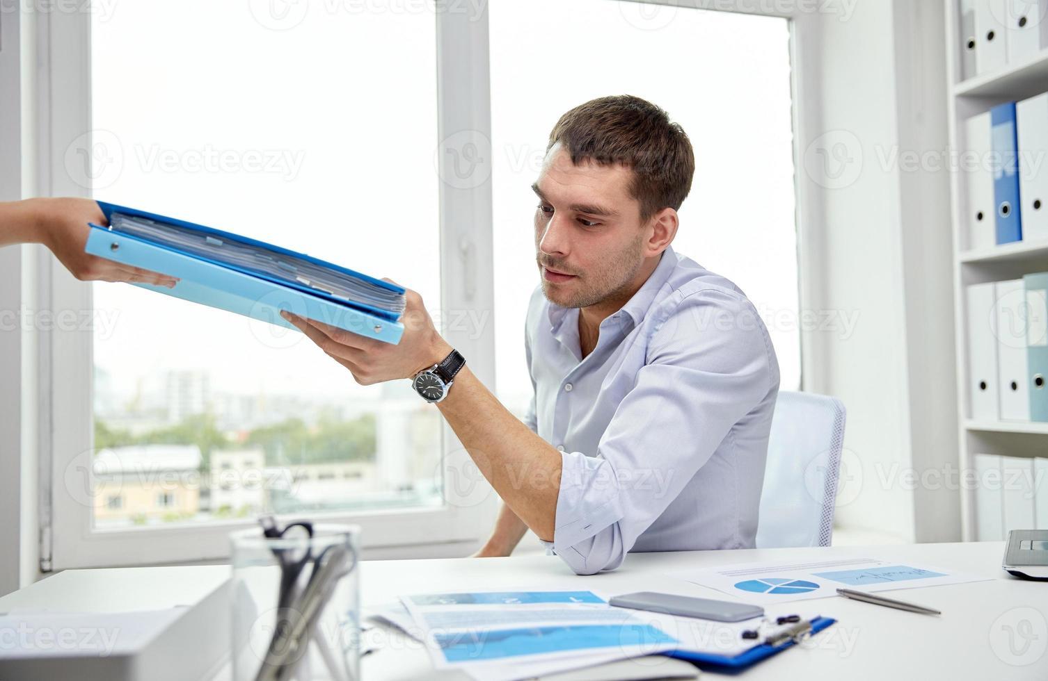 zakenman die documenten van secretaresse in bureau foto