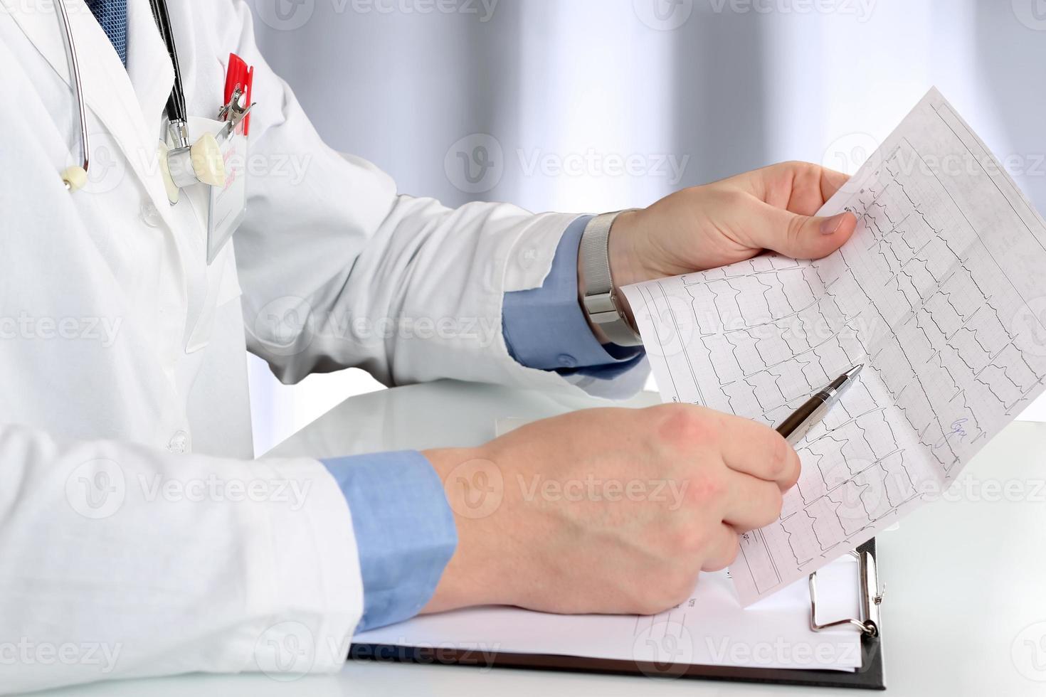 gezondheidszorg en geneeskundeconcept - arts met klembord analizing cardiogram foto