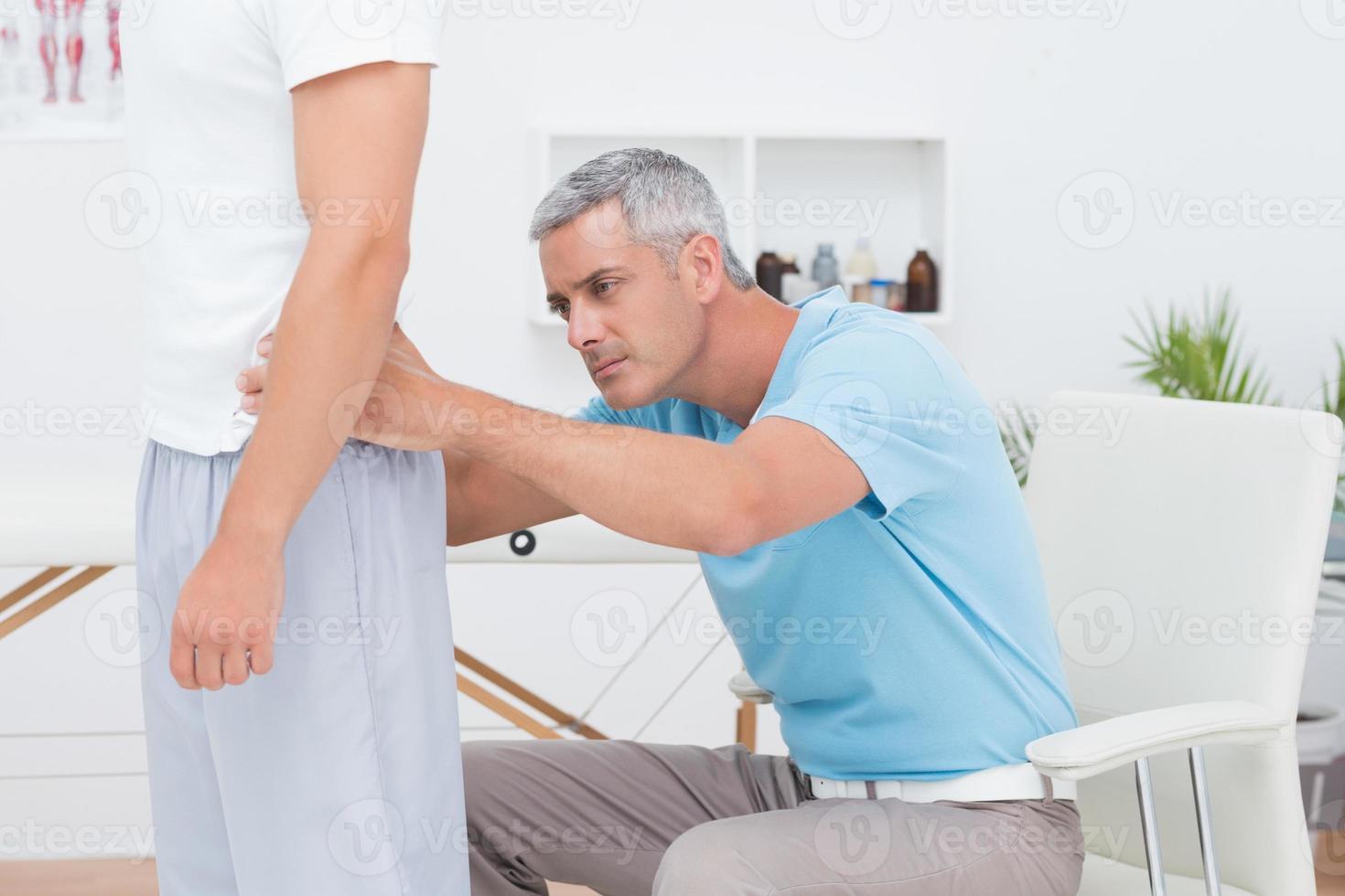 arts die zijn patiënt terug onderzoekt foto