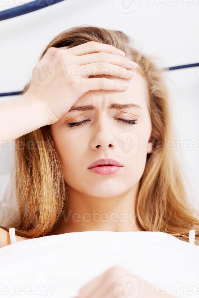 mooie casual blanke vrouw liggend in bed, haar voorhoofd aan te raken foto