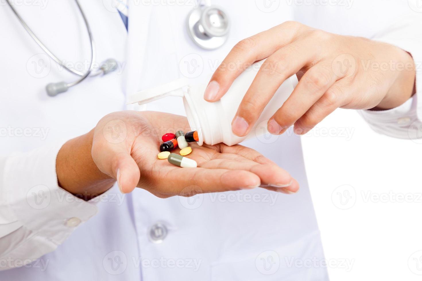 Aziatische mannelijke arts met pillen en apotheekfles foto