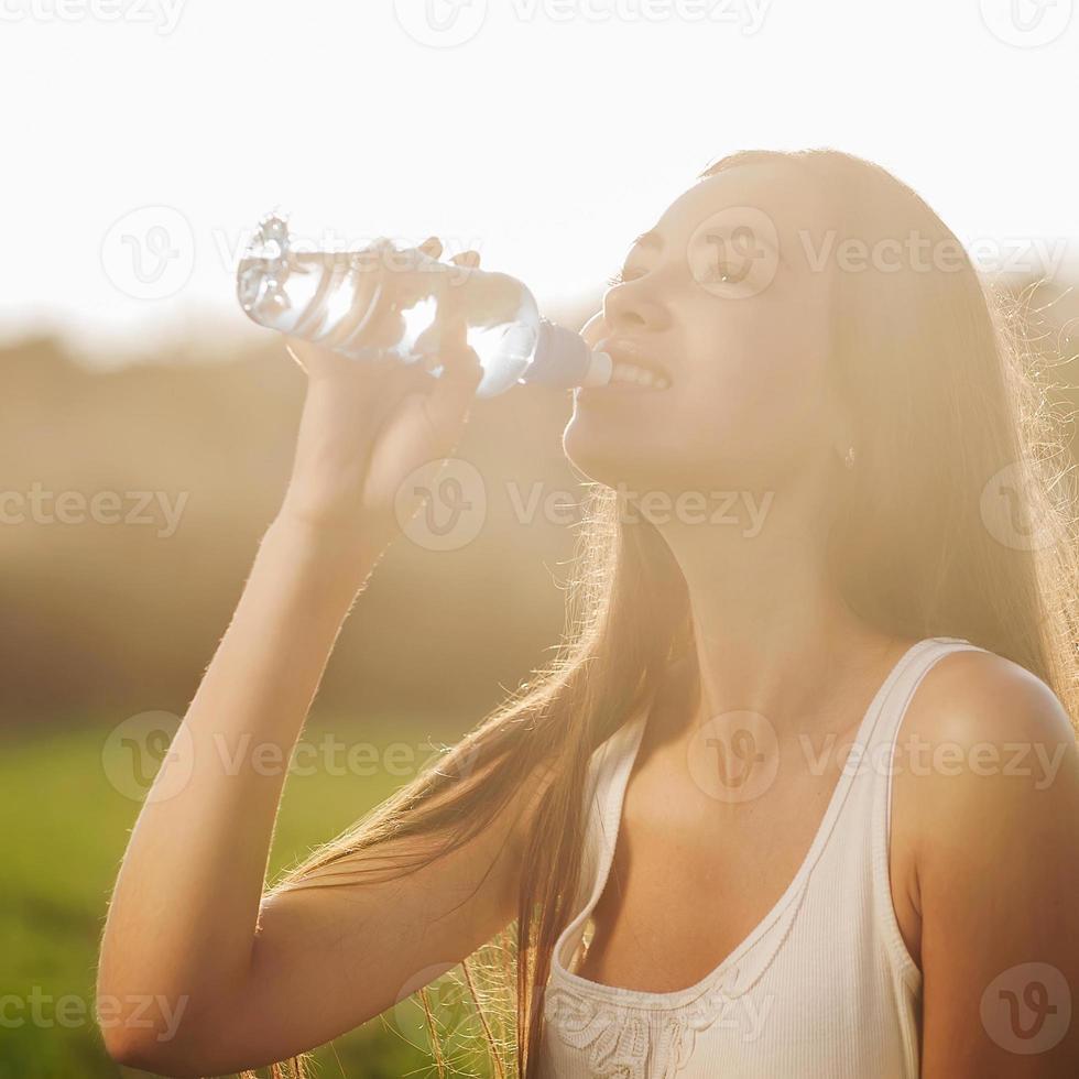 portret half gezicht van jonge vrouw drinkt water foto
