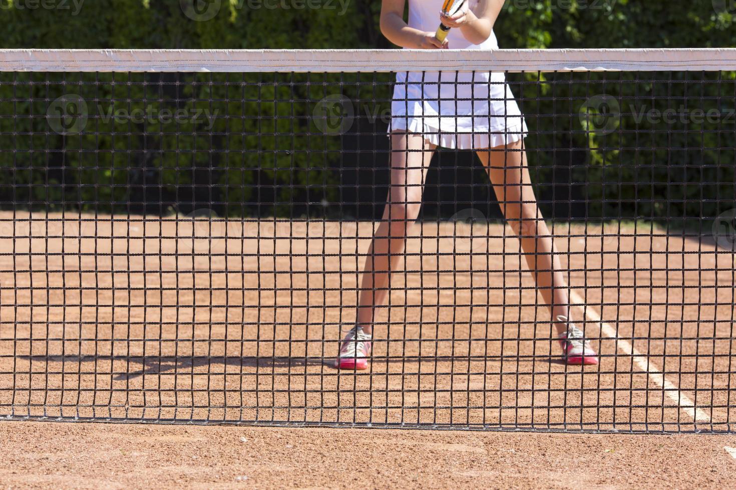 slanke benen van vrouwelijke tennisatleet achter visnetbarrière foto