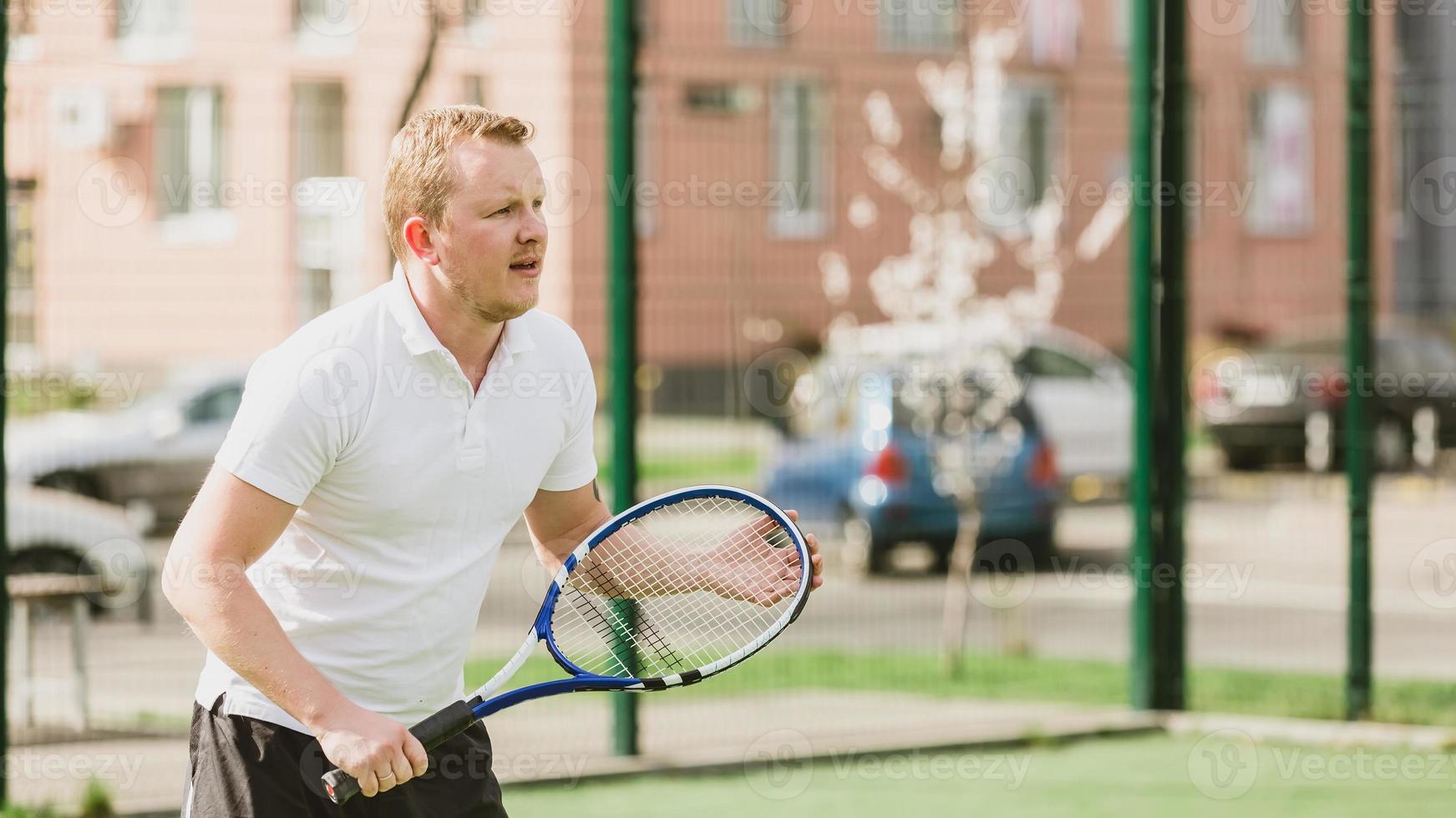 man tennissen buiten foto