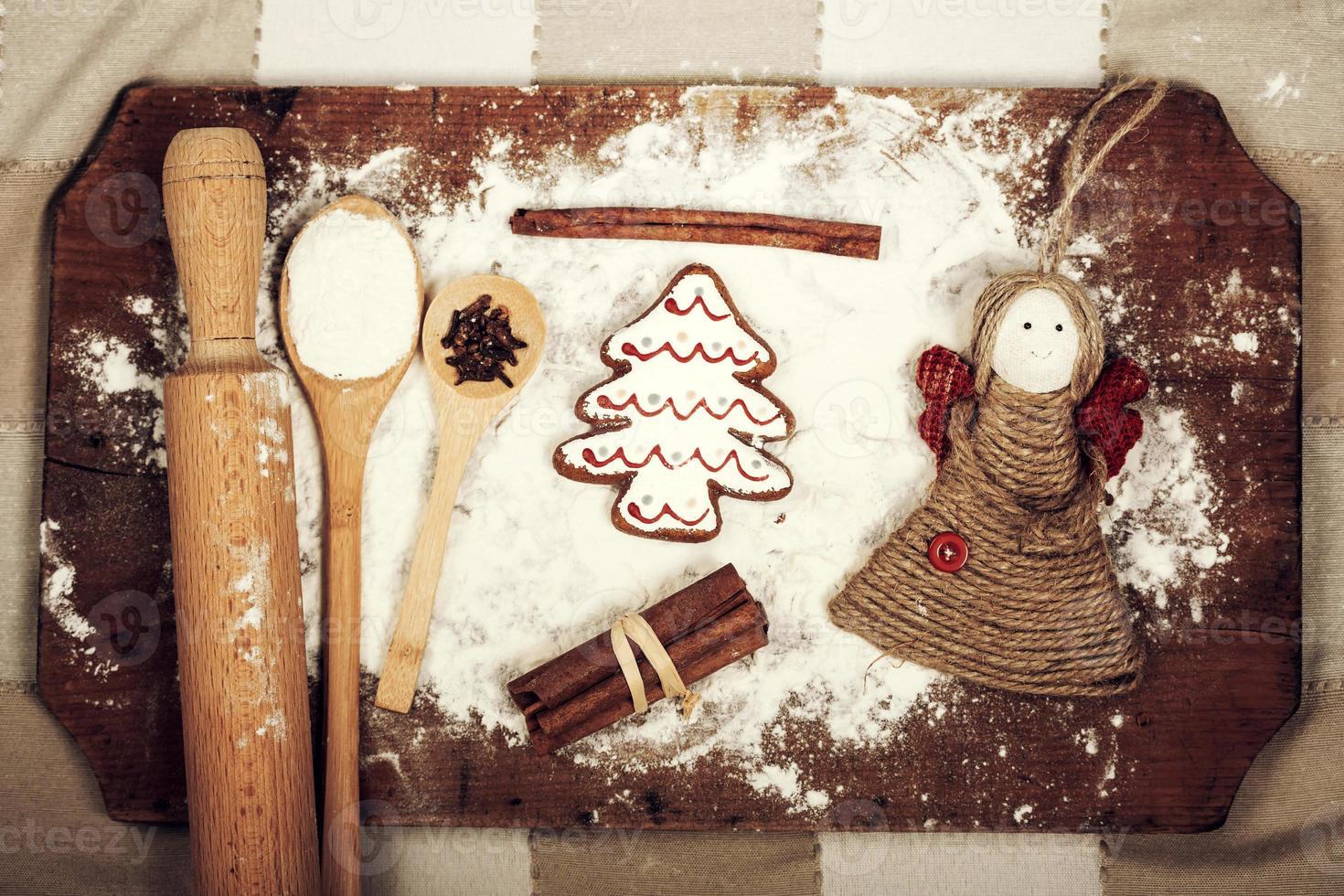 kerstkoekjes, specerijen en meel op houten snijplank foto