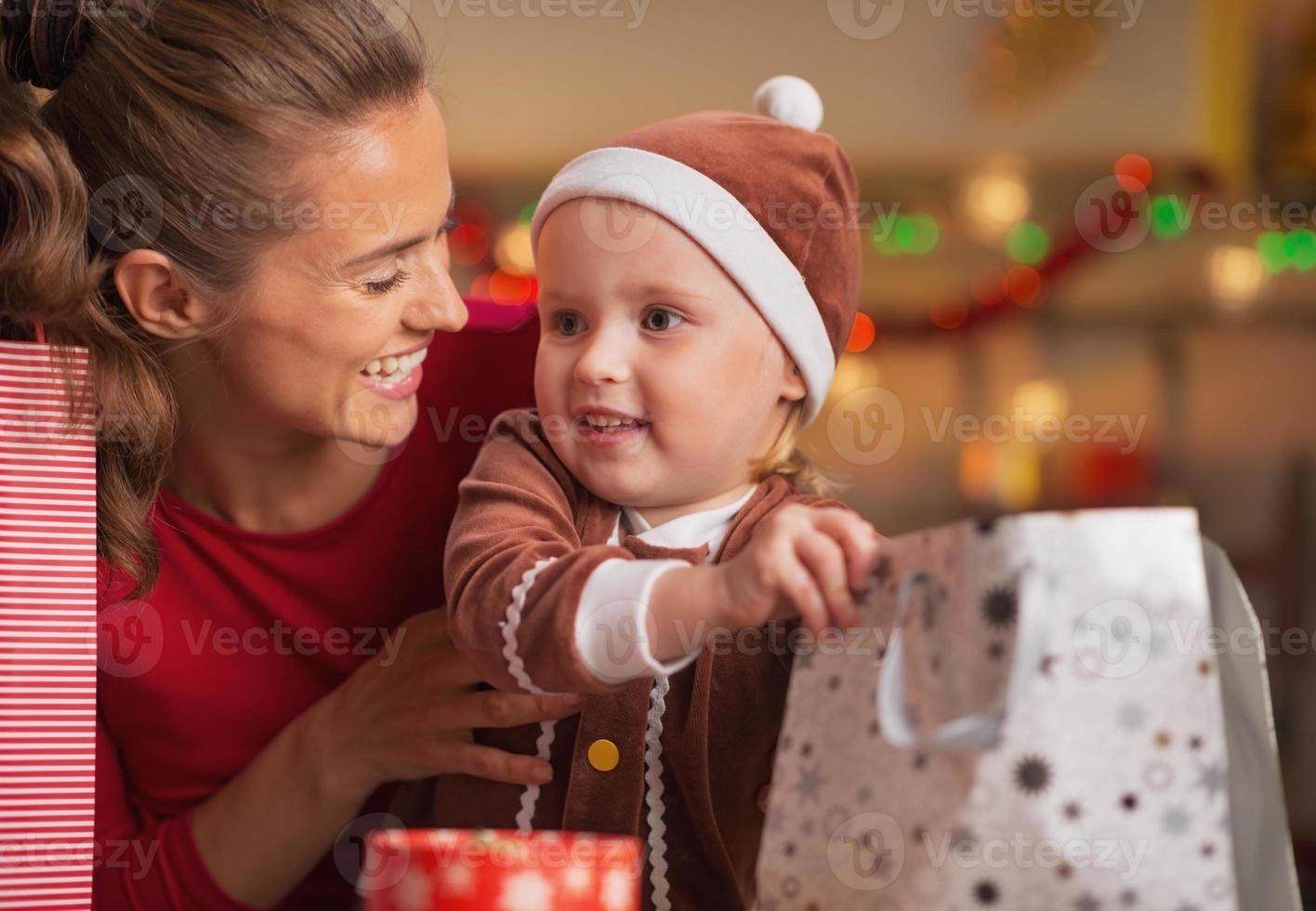 gelukkige moeder en baby het controleren van kerst boodschappentassen foto