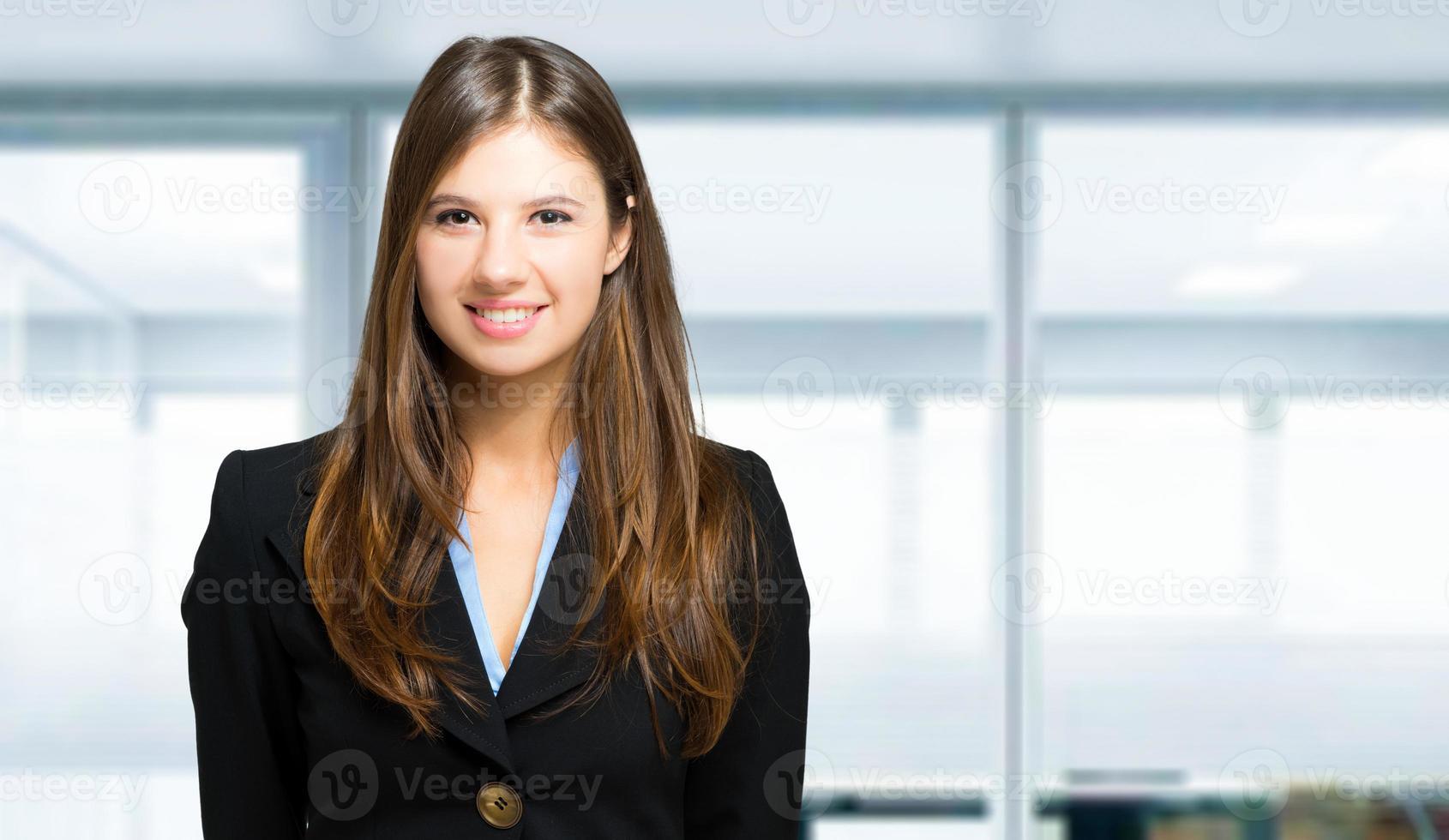 Glimlachende zakenvrouw in een modern kantoor foto