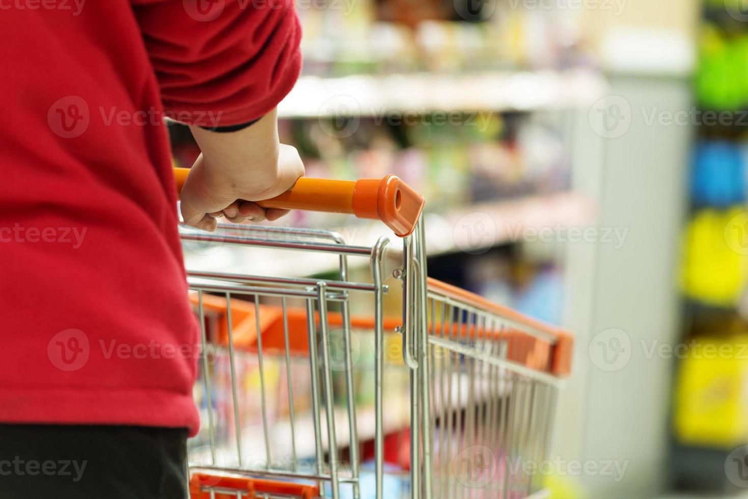dame duwt een winkelwagentje in de supermarkt. foto
