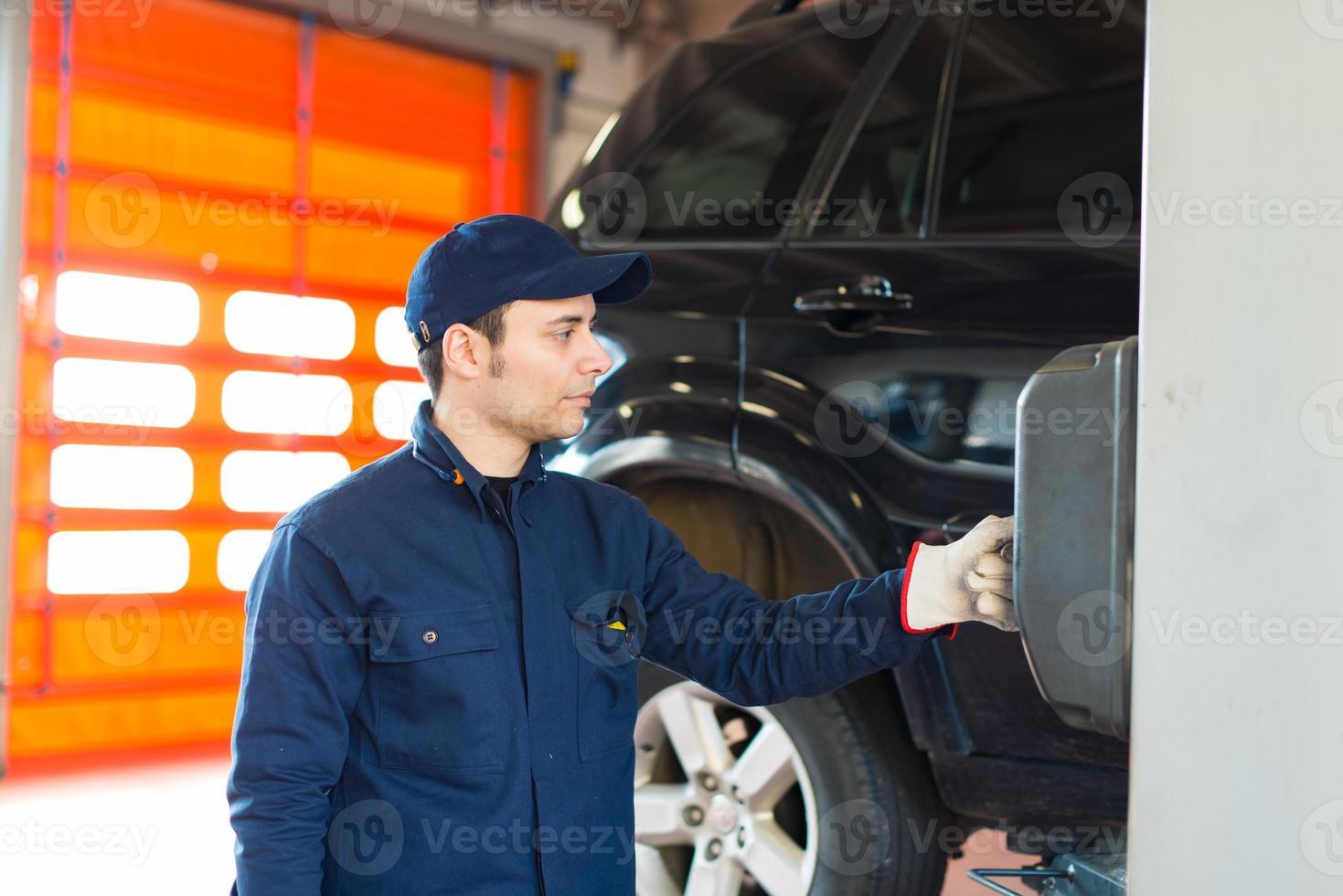 wiel van de monteur het veranderende auto in autoreparatiewerkplaats foto