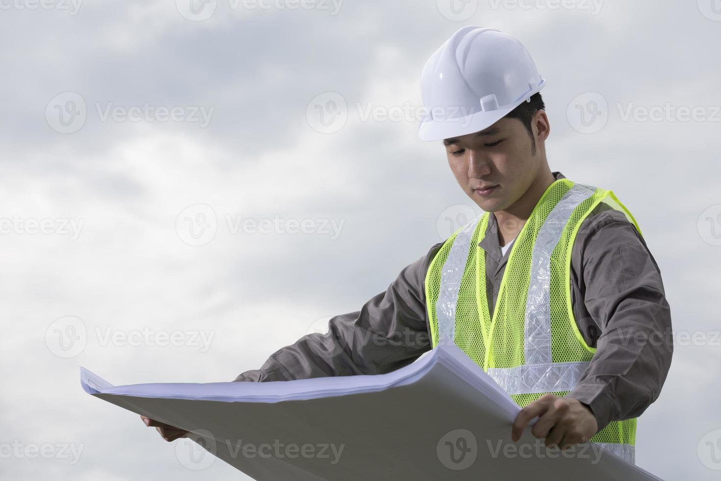 Aziatische industrieel ingenieur aan het werk dat plannen bekijkt. foto