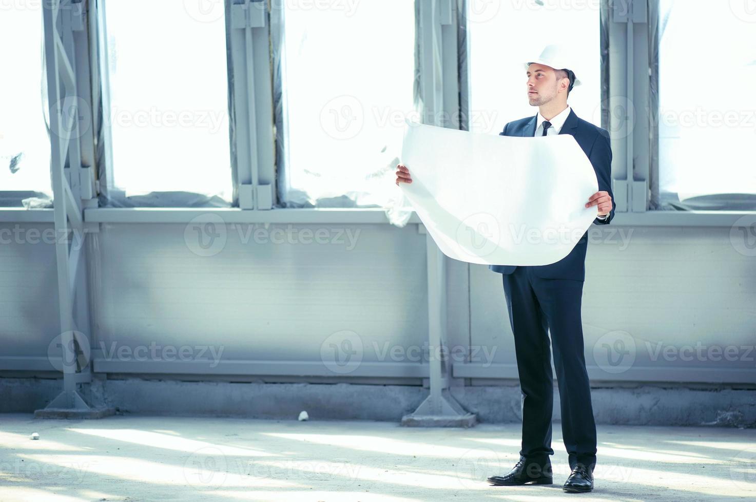 knappe jonge ingenieur denkt aan nieuw project foto