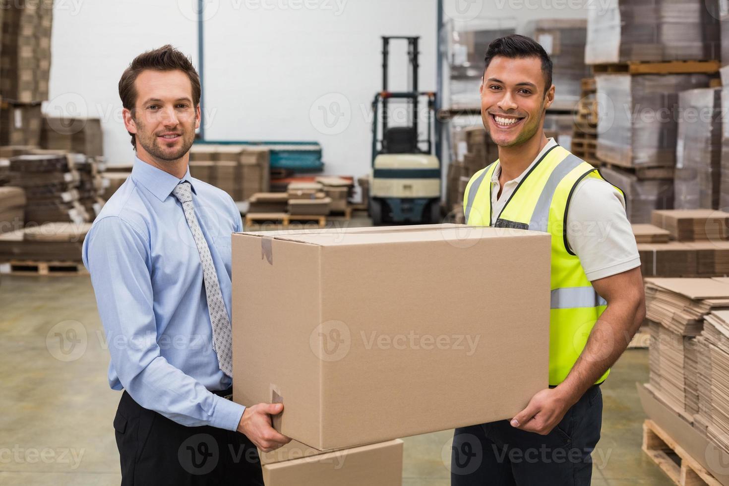 magazijnmedewerker en manager passeren van een doos foto