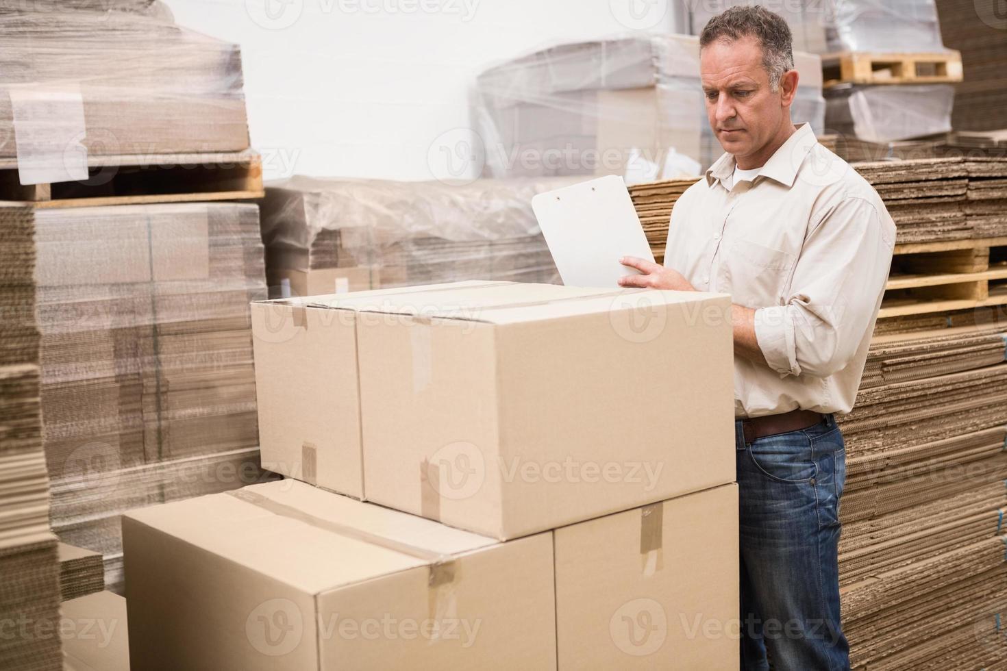 magazijnmedewerker zijn lijst op klembord controleren foto