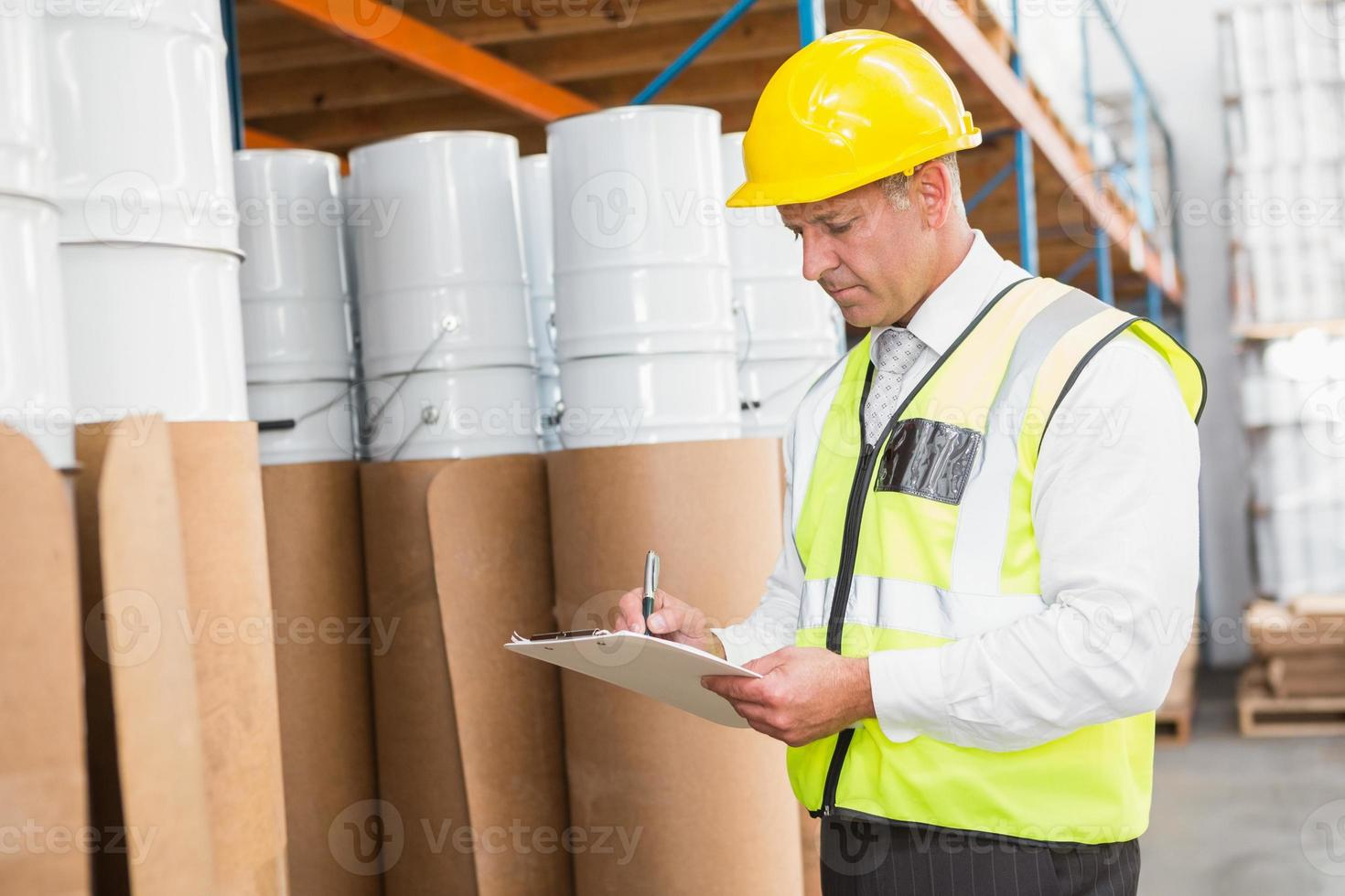 magazijnbeheerder die zijn lijst op klembord controleert foto