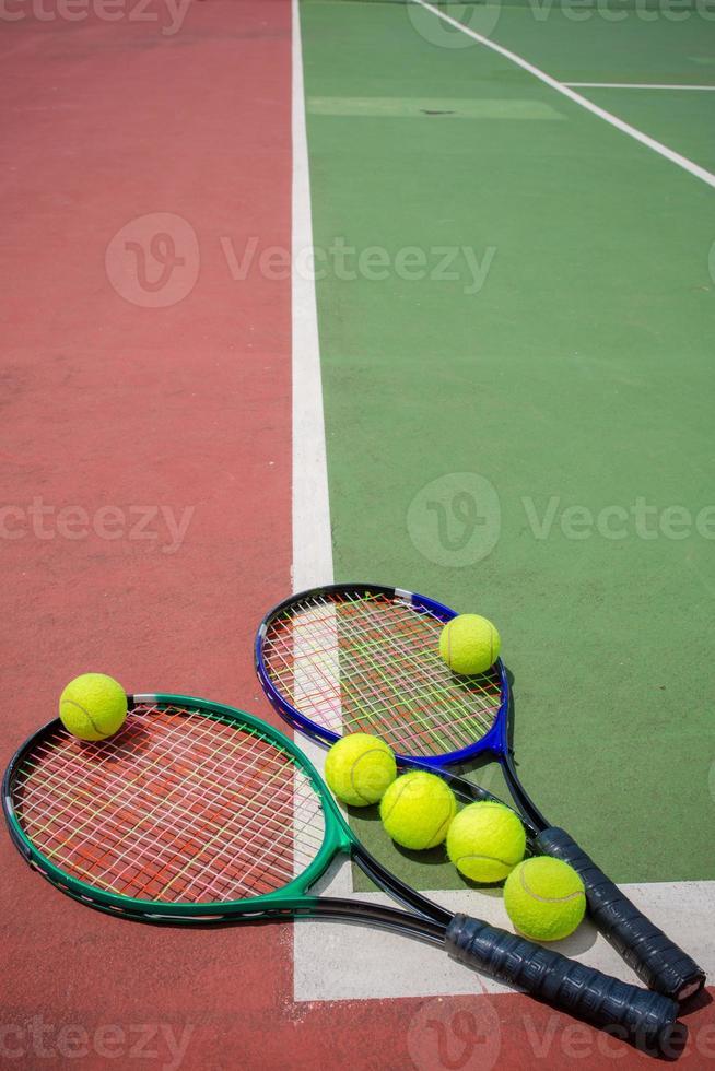 tennisracket en ballen op de tennisbaan foto