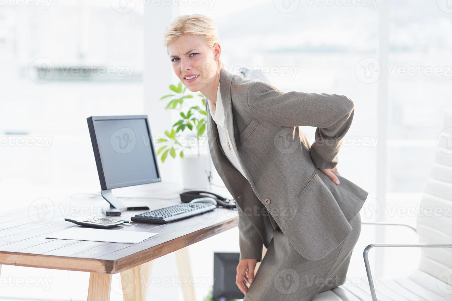 triest zakenvrouw met pijn in de onderrug foto