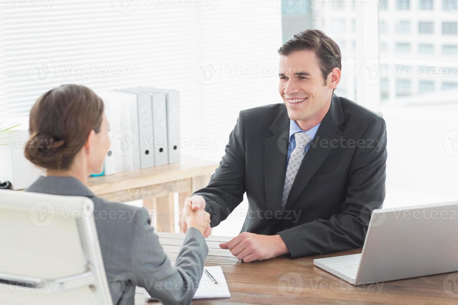 zakenman handen schudden met een zakenvrouw foto