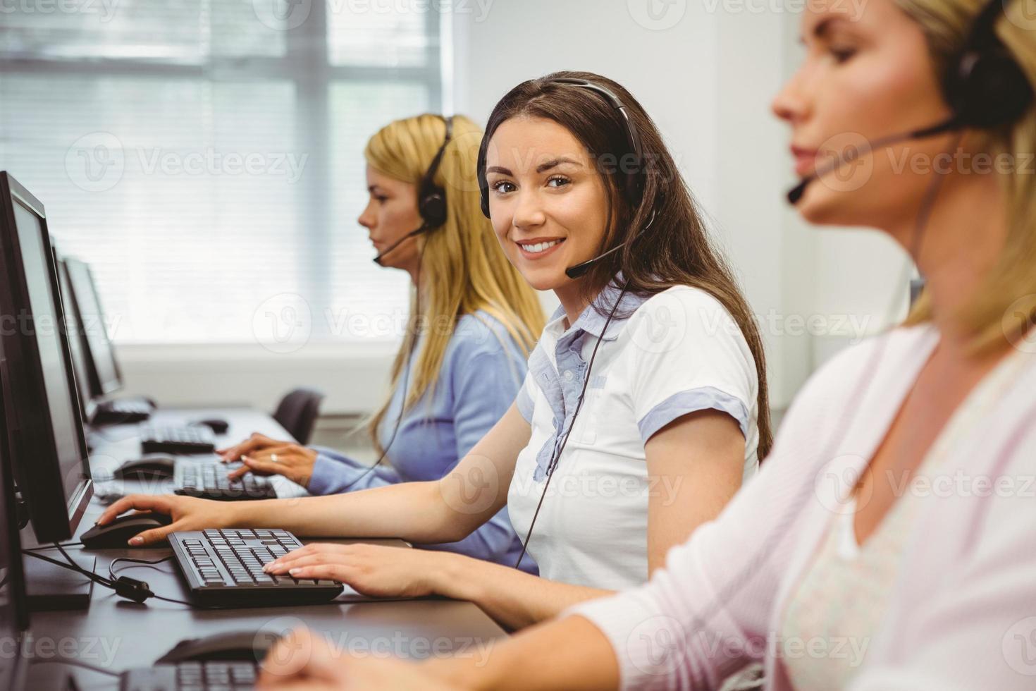 glimlachende callcentermedewerker die op de hoofdtelefoon spreekt foto