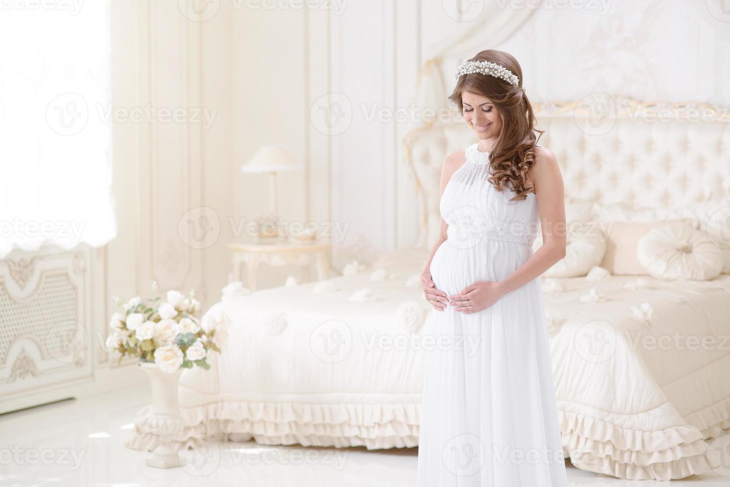 gelukkige zwangere vrouw in een licht interieur foto