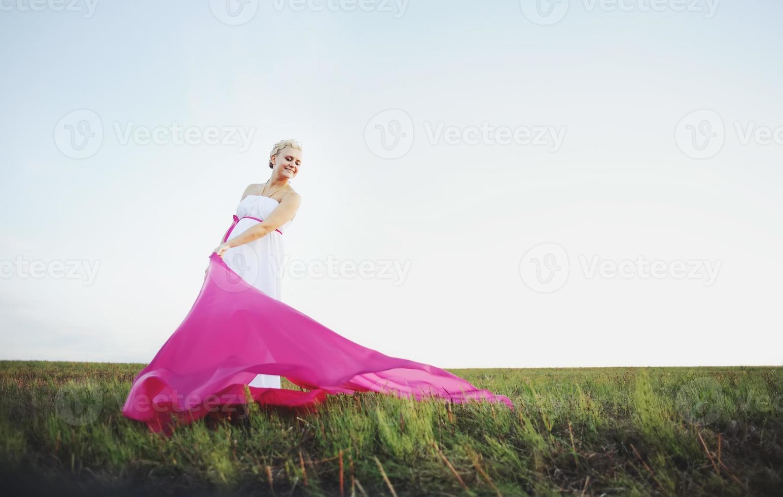 mooie zwangere jonge vrouw in Griekse witte jurk buiten foto